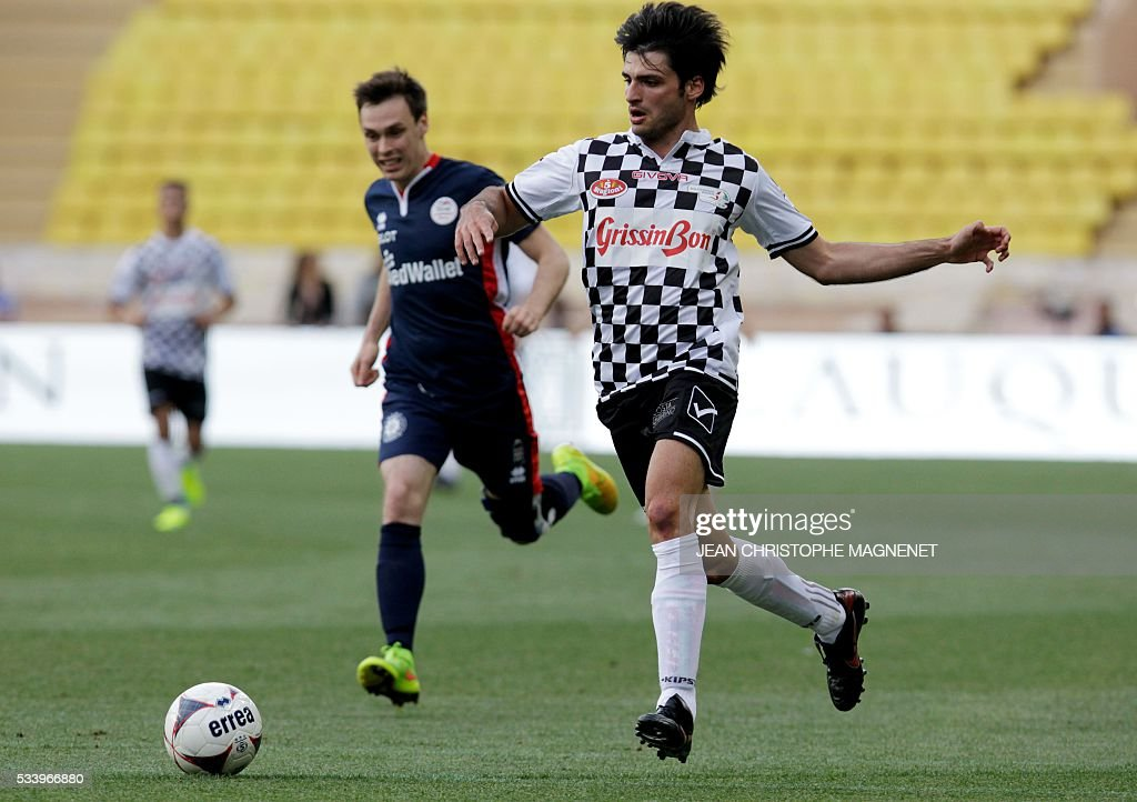 Spanish F1 driver Carlos Sainz Jr (R) controls the ball during a charity football match between Prince Albert's Star Team and the F1 'Nazionale Piloti' drivers' team, for the benefit of the 'Association Mondiale des Amis de l'Enfance' (Protection of Children Association) on May 24, 2016 at the Louis II Stadium, in Monaco. / AFP / JEAN