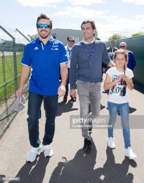 Part of this image has been pixellated to obscure the identity of the child Spanish F1 driver Fernando Alonso and Pedro de la Rosa attends the...