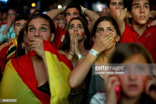 Spanish fans react while watching their team play against the Chileans on the giant screen showing the FIFA World Cup match between Spain and Chile...