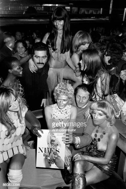 Spanish fashion designer Paco Rabanne surrounded by models wearing metal dresses presents his book 'Nues' on December 3 1969 at the Crazy Horse...