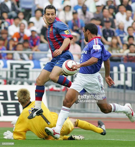 Spanish FC Barcelona forward Ludovic Giuly of France fights for the ball against Japan's Yokohama F Marinos' Goalkeeper Tatsuya Enomoto and defender...