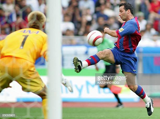 Spanish FC Barcelona forward Ludovic Giuly of France shoots the ball against Japan's Yokohama F Marinos' Goalkeeper Tatsuya Enomoto during a 1st half...