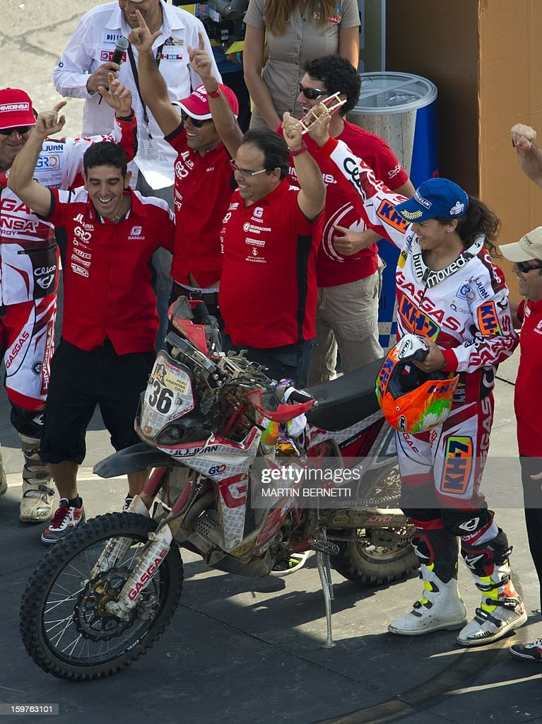 Spanish female pilot Laia Sanz (R) celebrates at the 2013 Dakar Rally podium, in Santiago,Chile, on January 20, 2013. Stephane Peterhansel claimed a record fifth Dakar Rally drivers title, and 11th overall of his career, while French compatriot Cyril Despres captured a fifth motorcycling crown.