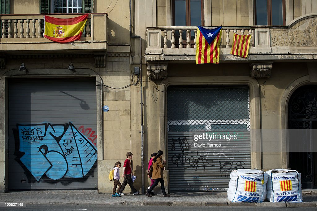 A Spanish flag (L) and a Pro-independent Catalonia's flag are seen hanged as a family walks beneath them on November 22, 2012 in Barcelona, Spain. Over 5 million Catalans will be voting in Parliamentary elections on November 25, with opinion polls showing majority support for pro-independence parties.