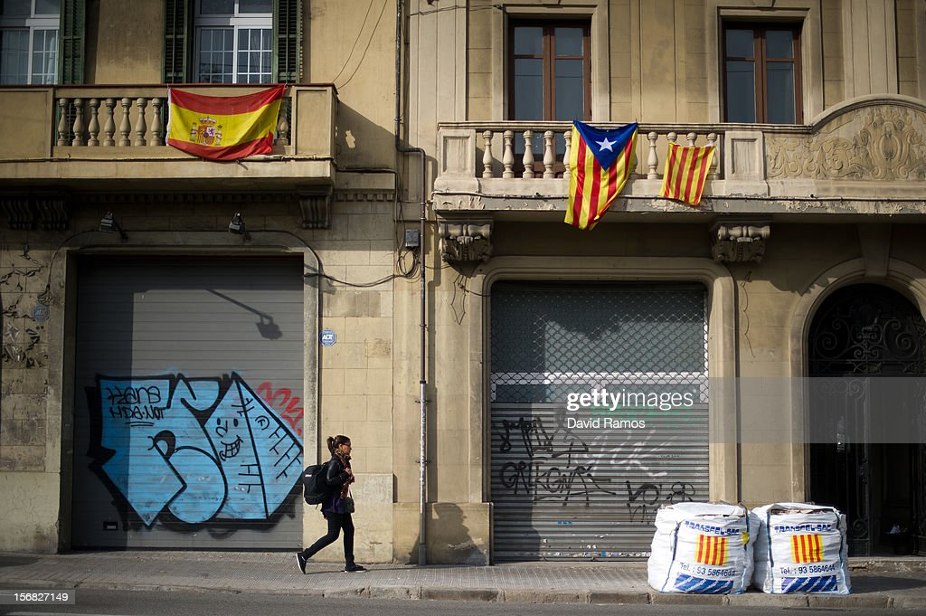 A Spanish flag (L) and a Pro-independent Catalonia's flag are seen hanged as a woman walks beneath them on November 22, 2012 in Barcelona, Spain. Over 5 million Catalans will be voting in Parliamentary elections on November 25, with opinion polls showing majority support for pro-independence parties.