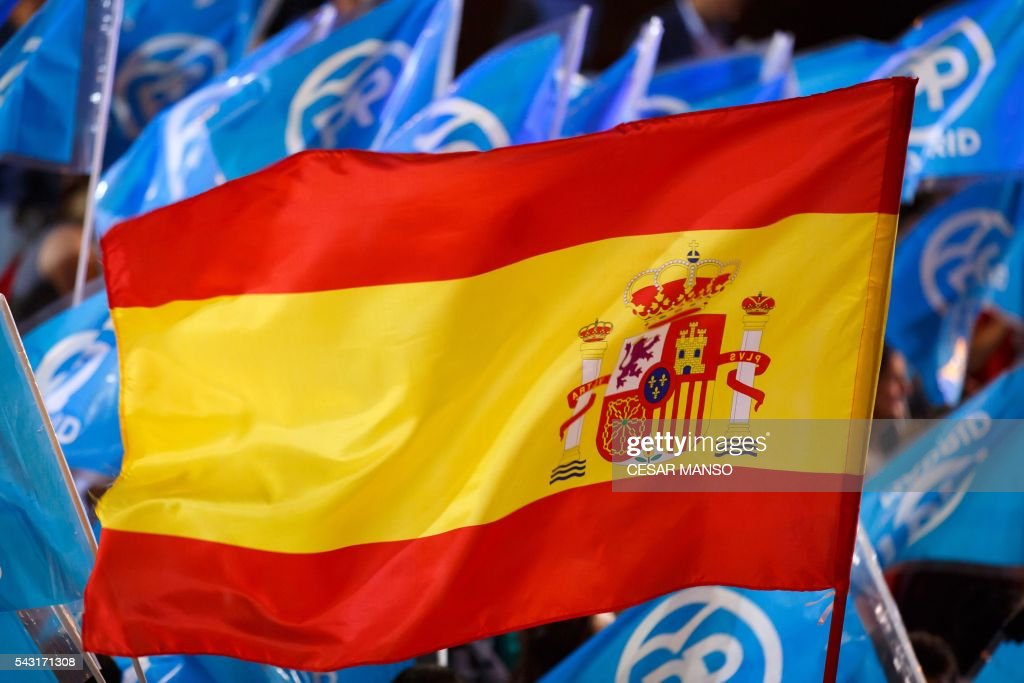 A Spanish flag flies amongst flags of the Popular Party (PP) outside the PP headquarters during Spain's general election in Madrid on June 26, 2016. Spain's second elections in six months was due to conclude on June 26 in much the same way as they did in December, with the incumbent conservatives winning tailed by the Socialist party, partial results showed. / AFP / CESAR