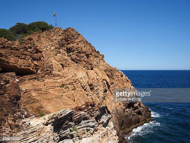 Spanish flag on rocks near Sa Tuna, Gerona