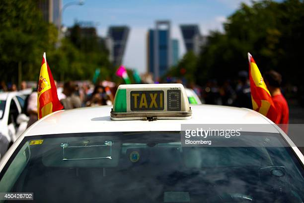 Spanish flags fly from a taxi cab during a demonstration by cabbies to protest against the Uber Technologies Inc taxi app in central Madrid Spain on...