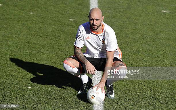 Spanish football club Valencia CF's new signing Italian striker Simone Zaza poses with a ball during his official presentation at the Valencia Sports...