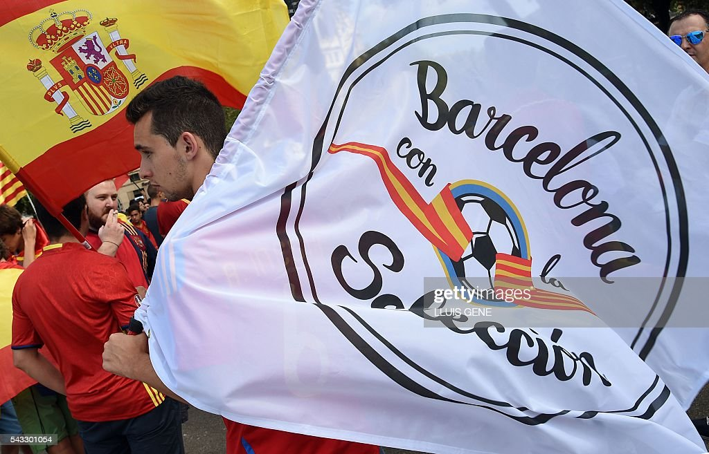 Spanish football team supporters hold a Spanish flag and a flag reading, ' Barcelona with the selection' at Catalunya square in Barcelona on June 27, 2016 before the Euro 2016 football match between Spain and Italy held at the Stade de France stadium in Paris, France. / AFP / LLUIS