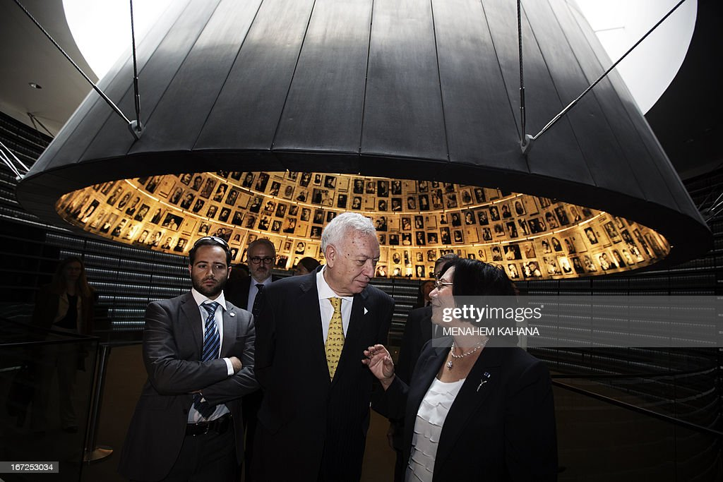 Spanish Foreign Minister, Jose Manuel Garcia-Margallo (C) listens to Perla Hazan (R), director of the Yad Vashem Holocaust memorial, as he visits the Hall of Names which commemorates the six million Jews killed by the Nazis during World War II, in Jerusalem on April 23, 2013. AFP PHOTO/MENAHEM KAHANA