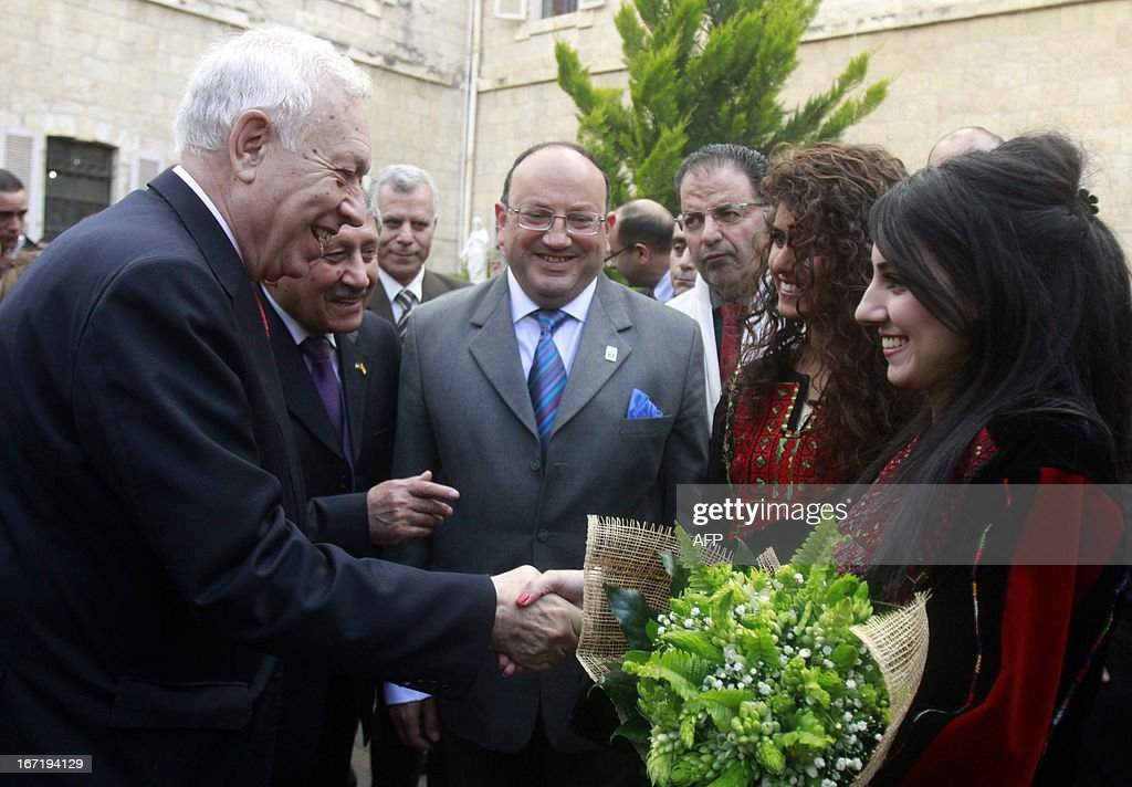 Spanish Foreign Minister Jose Manuel Garcia-Margallo (L) receives a bouquet of flowers from a student during his visit to the University of Bethlehem in the biblical West Bank city on April 22, 2013. AFP PHOTO/MUSA AL SHAER