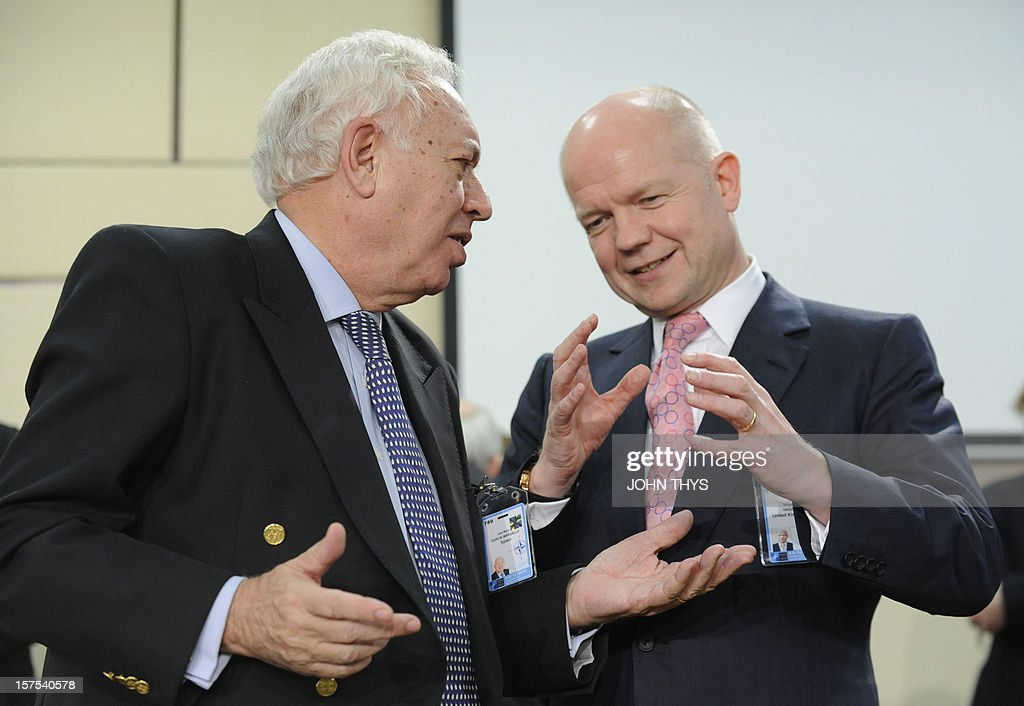 Spanish Foreign Minister Jose Manuel Garcia-Margallo speaks with British Foreign and Commonwealth Affairs Secretary William Hague on December 4, 2012 at North Atlantic Treaty Organization (NATO) headquarters in Brussels during a meeting of foreign ministers from the 28 NATO member-countries to discuss Syria and Turkey's request for Patriot missiles to be deployed protectively on the Turkish-Syrian border.