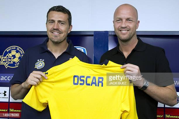 Spanish former footballer Oscar Garcia new manager coach of the Maccabi Tel Aviv football club and team manager Jordi Cruyff hold up a team jersey...