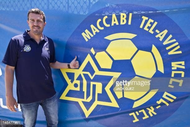 Spanish former footballer Oscar Garcia poses next to the logo of the Maccabi Tel Aviv football club where he is now manager before a press conference...