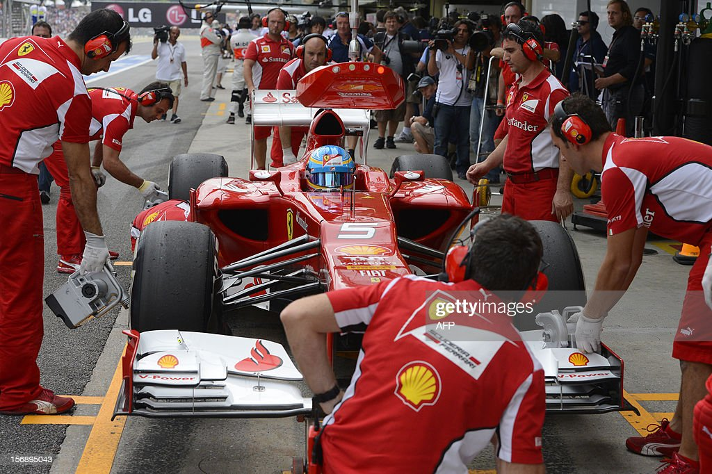 Spanish Formula One driver Fernando Alonso has his Ferrari tuned at the pits on November 24, 2012 during the free practices for the Brazilian GP on Sunday at the Interlagos racetrack in Sao Paulo, Brazil. AFP PHOTO/YASUYOSHI CHIBA