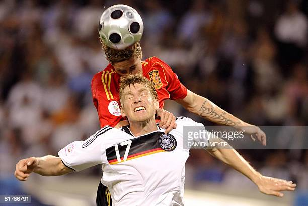 Spanish forward Fernando Torres heads the ball ahead of German defender Per Mertesacker during the Euro 2008 championships final football match...