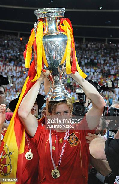 Spanish forward Fernando Torres holds up the Trophy after Spain won the Euro 2008 championships final football match against Germany on June 29 2008...