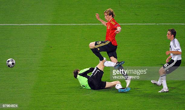 Spanish forward Fernando Torres kicks the ball and scores in front of German goalkeeper Jens Lehmann and German defender Philipp Lahm during the Euro...