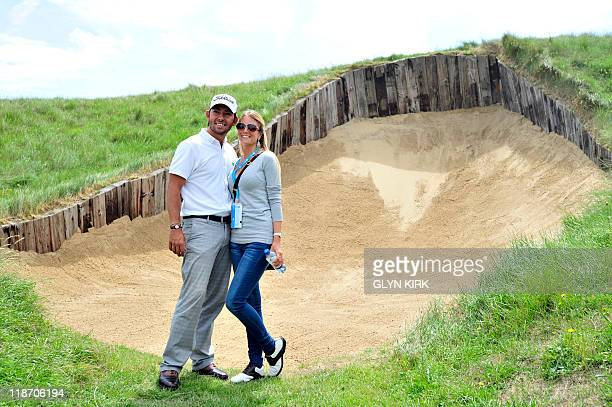 Spanish golfer Pablo Larrazabal poses for a photo with his girlfriend Gala by the bunker on the 4th hole during practice for The Open championship at...