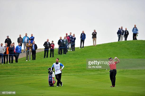 Spanish golfer Pablo Larrazabal watches his approach shot to the 1st green in his match against French golfer Victor Dubuisson during the first day...