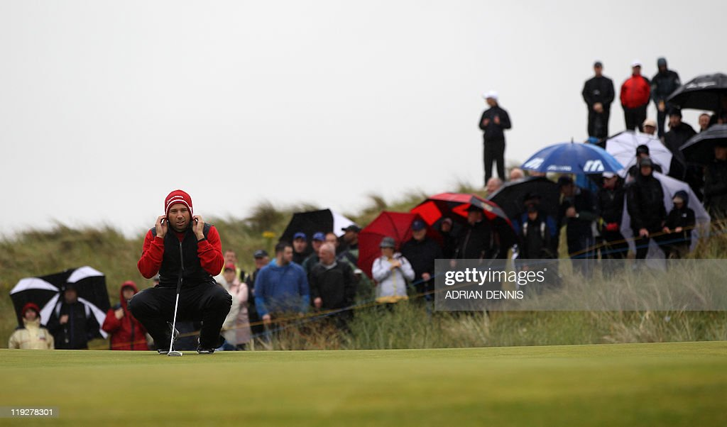 Spanish golfer Sergio Garcia adjusts his hat on the 1st green on the third day of the 140th British Open Golf championship at Royal St George's in Sandwich, Kent, south east England, on July 16, 2011.