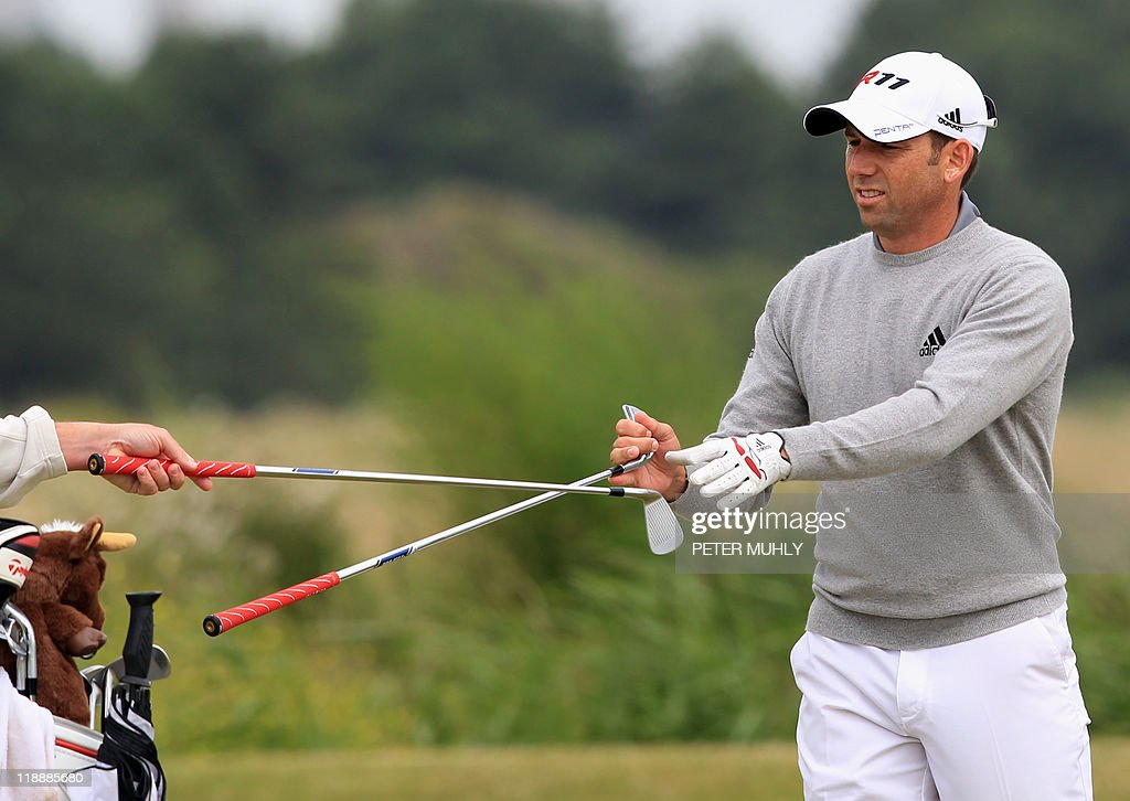 Spanish golfer Sergio Garcia changes clubs on the 14th green during practice for the 140th British Open Golf championship at Royal St George's in Sandwich, Kent, south east England, on July 12, 2011.