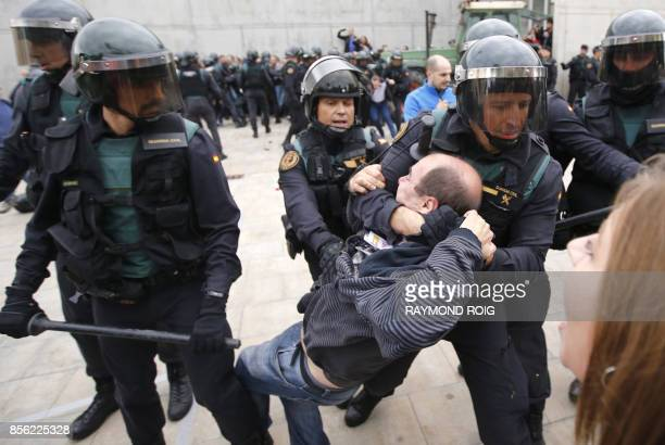 TOPSHOT Spanish Guardia Civil guards drag a man outside a polling station in Sant Julia de Ramis where Catalan president was supposed to vote on...