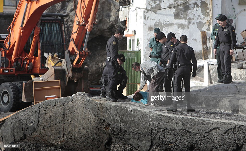 Spanish Guardia Civil members evict neighbors from their home in the fishing village of Chovito on the Spanish Canary Island of Tenerife, on November 16, 2012. Six neighbors have been on hunger strike to protest a court decision requiring the demolition of their houses according to the Spanish Coastal Law.