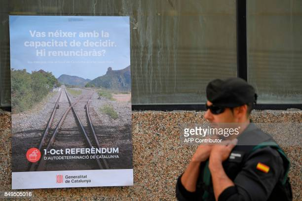 A Spanish Guardia Civil stands guard next to a proreferendum poster during a search for propaganda supporting Catalonia's independence referendum at...
