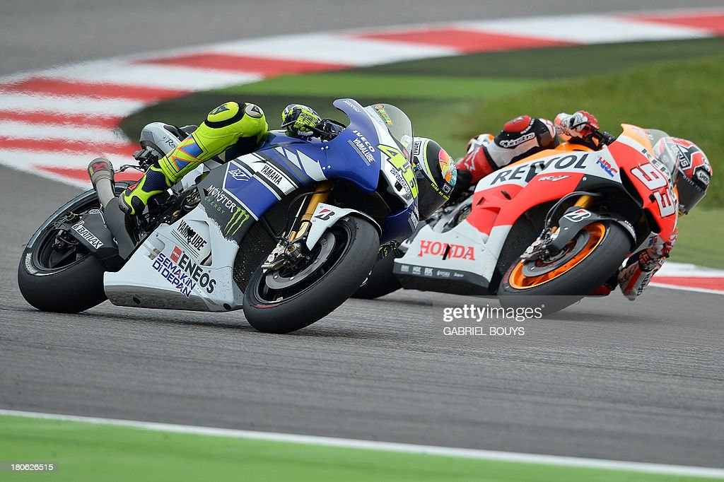 Spanish Honda riders Marc Marquez (R) outpasses Yamaha Valentino Rossi of Italy during the San Marino MotoGP Grand Prix on September 15, 2013 at the Misano world circuit in Misano Adriatico. Yamaha rider Jorge Lorenzo of Spain won the race ahead of Spanish Honda riders Marc Marquez, second place and Dani Pedrosa, third. AFP PHOTO / GABRIEL BOUYS