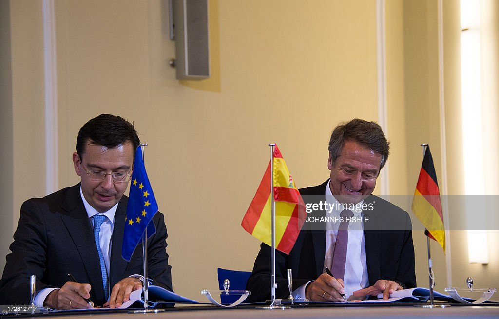Spanish ICO bank CEO Roman Escolano (L) and CEO of German bank KfW, Ulrich Schroeder sign an agreement outlining financial support to Spanish small and medium-sized businesses in Berlin on July 4, 2013. Germany and Spain signed an agreement to boost access to affordable credit for small and medium enterprises in the recession-hit southern European country in a bid to foster growth and create jobs. AFP PHOTO / JOHANNES EISELE