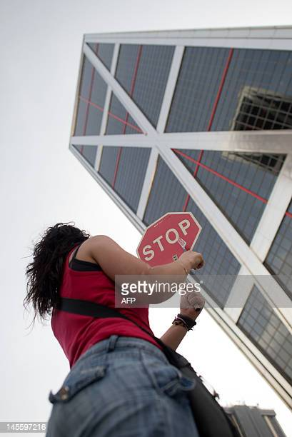A Spanish indignant protester holds a STOP sign during a demonstration against banking abuses in front of the headquarters of Spaish bank Bankia on...