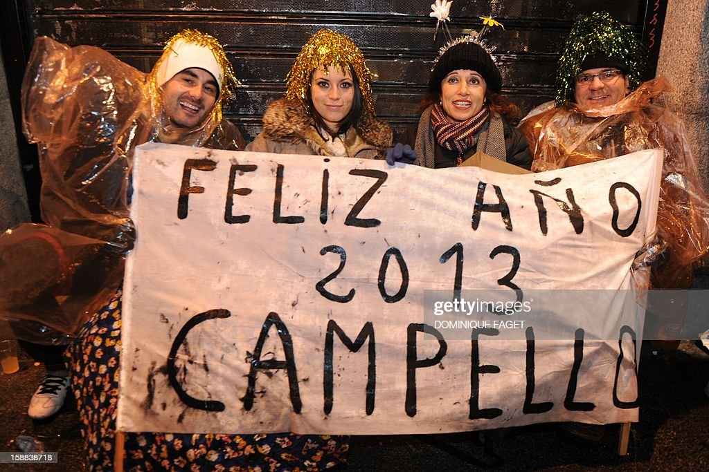 Spanish inhabitants of Campello, a town near southeastern city of Alicante, pose with a banner reading 'Happy New Year 2013' as they celebrate the beginning of New Year's Day under the rain at Puerta del Sol in Madrid on December 31, 2012.