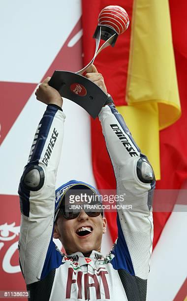 Spanish Jorge Lorenzo raises his trophy as he celebrates on the podium after he finished second of the French Moto GP on May 18 2008 at the Le Mans'...