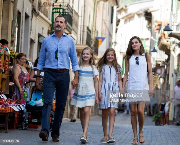 TOPSHOT Spanish King Felipe VI his wife Queen Letizia and their daughters Spanish crown princess Leonor and princess Sofia walk down a street in the...