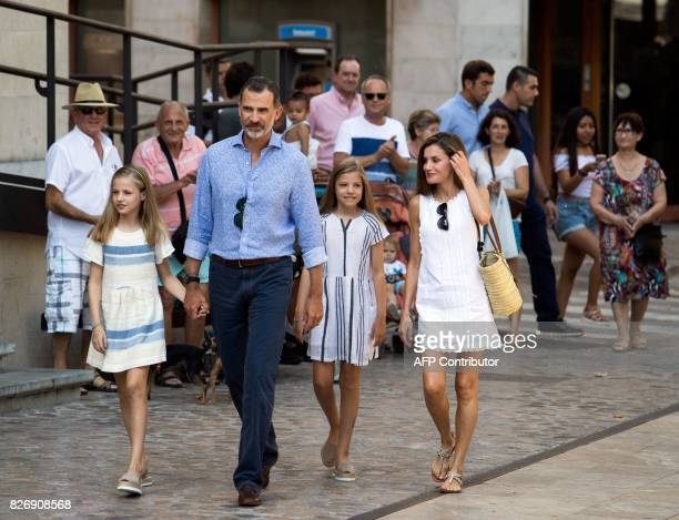 Spanish King Felipe VI his wife Queen Letizia and their daughters Spanish crown princess Leonor and princess Sofia walk down a street in the village...