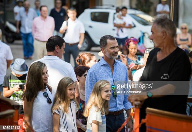 Spanish King Felipe VI his wife Queen Letizia and their daughters Spanish crown princess Leonor and princess Sofia walk in a street during their...