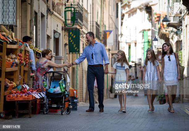 Spanish King Felipe VI shakes hands with a woman as he walks down a street with his wife Queen Letizia and their daughters Spanish crown princess...