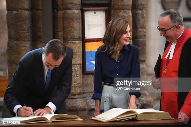 Spanish King Felipe VI signs the visitors book as Spanish Queen Letizia and the Dean of Westminster Abbey John Hall share a light moment after laying...