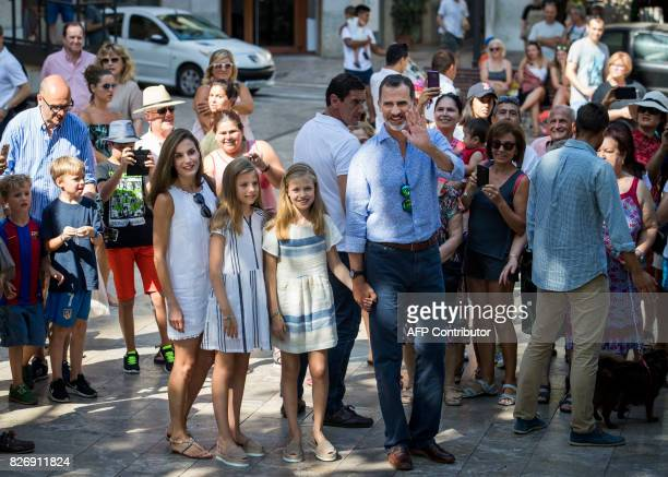 Spanish King Felipe VI wave to surrounding people as he walks with his family Queen Letizia and their daughters Spanish crown princess Leonor and...