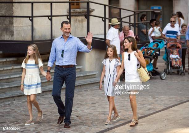 Spanish King Felipe VI waves as he walks down a street with his wife Queen Letizia and their daughters Spanish crown princess Leonor and princess...