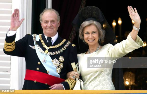 Spanish King Juan Carlos and Queen Sofia wave as they appear on the balcony of the royal palace after the wedding ceremony of Crown Prince Feleipe de...