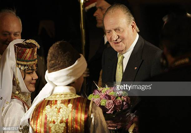 Spanish King Juan Carlos receives a bouquet of flowers from Lebanese children in traditional costumes upon his arrival at Beirut international...