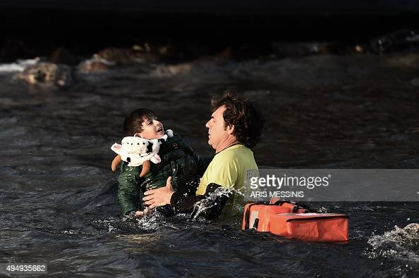 A Spanish lifeguard saves a migrant child as the boat he had boarded with other migrants and refugees sinks off the Greek island of Lesbos after...