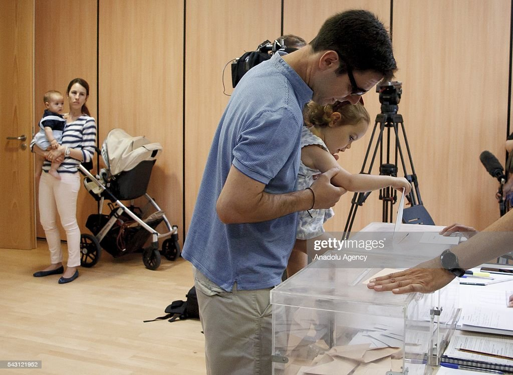 A Spanish man casts his ballot with his daughter during the Spanish General elections at a polling station in Madrid on June 26, 2016.