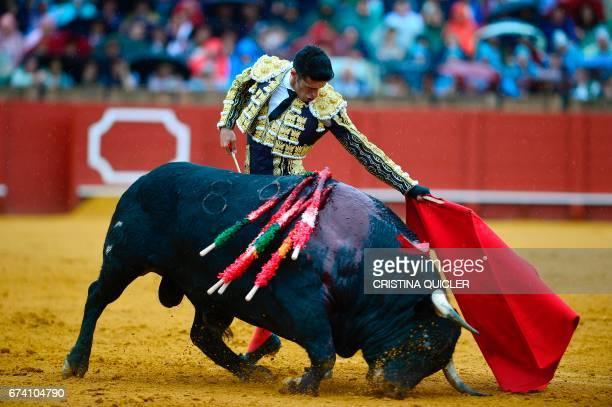 Spanish matador Alejandro Talavante performs a pass with muleta on a bull during a bullfight at the Maestranza bullring in Sevilla on April 27 2017 /...