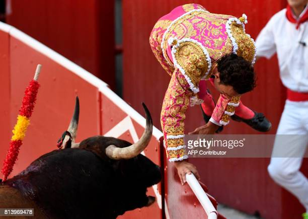 TOPSHOT Spanish matador Antonio Ferrera jumps over a berrier as he is chased by a Nunez del Cuvillo's fighting bull during the seventh bullfight of...