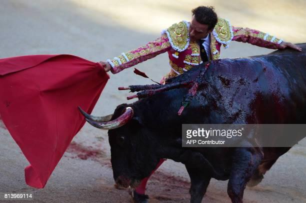 Spanish matador Antonio Ferrera performs a pass on a Nunez del Cuvillo's fighting bull during the seventh bullfight of the San Fermin Festival in...