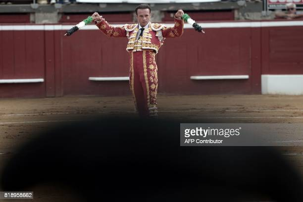 Spanish matador Antonio Ferrera raises banderilla sticks as he fights a Juan Pedro Domecq bull at the Plumacon Arena in MontdeMarsan during the...